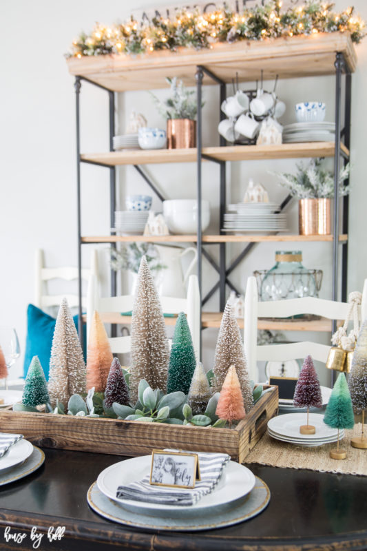 Mini trees on a wooden tray with succulents on the dining room table, and open shelving with lights on it.