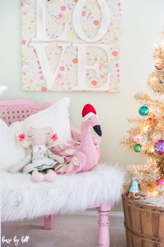 A love picture on the wall, with a little doll and flamingo on a pink chair under the picture.