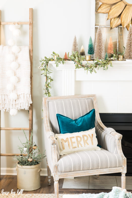 Turquoise blue velvet pillows on the armchairs in front of the fireplace.