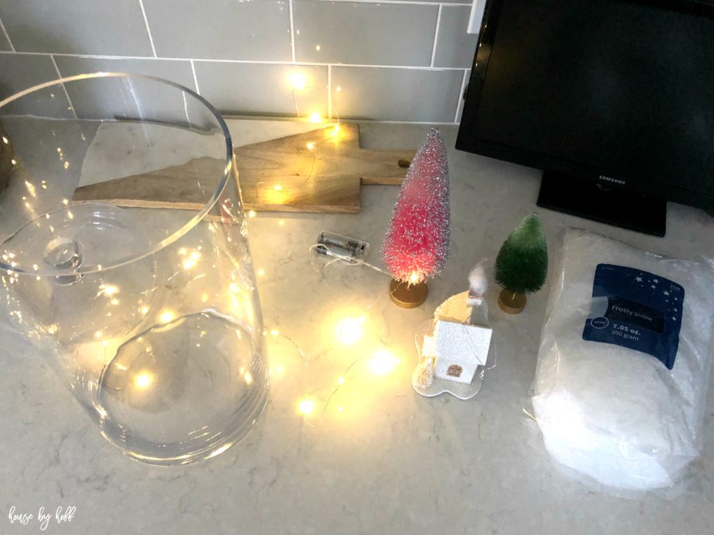 A clear glass jar with mini trees beside it and cotton on the kitchen counter.