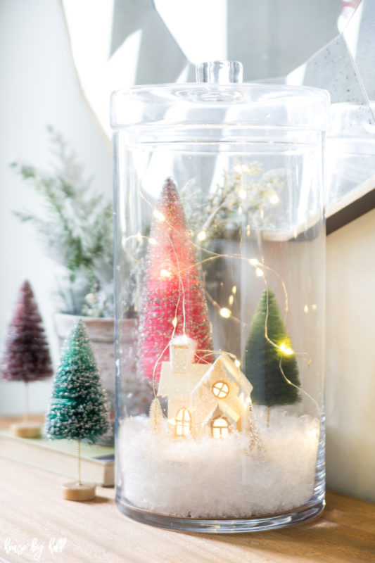 Mini house in a glass jar with trees and lights on the table.