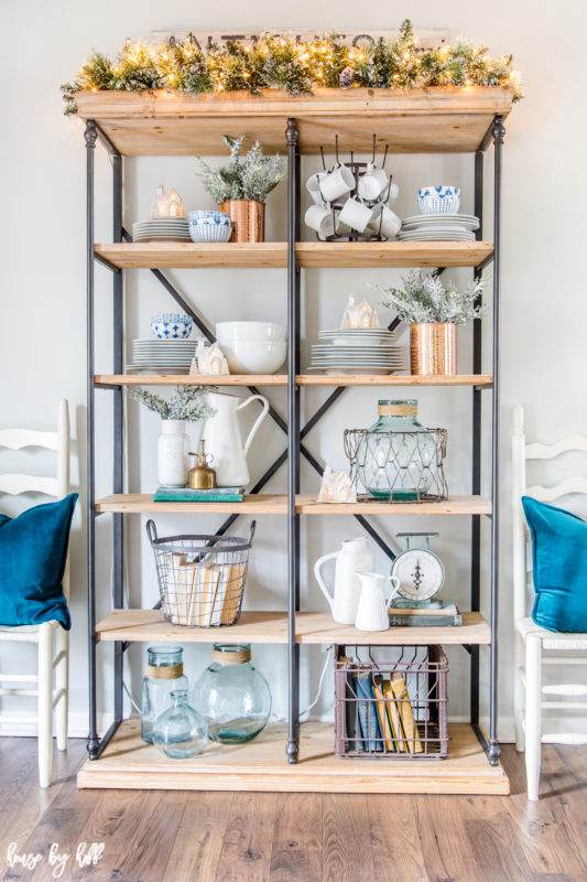 Open shelving unit with steel and wood, every shelf filled with cups, plates and glass.
