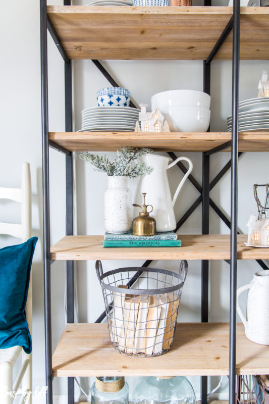 Open shelves with metal basket on the bottom filled with books, a white pitcher on the middle shelf, and plates and bowls on the top shelf.