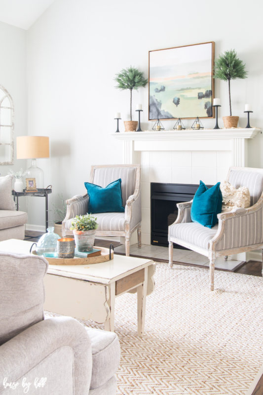Bright and Simple Winter Living Room with two white armchairs flanking a fireplace.