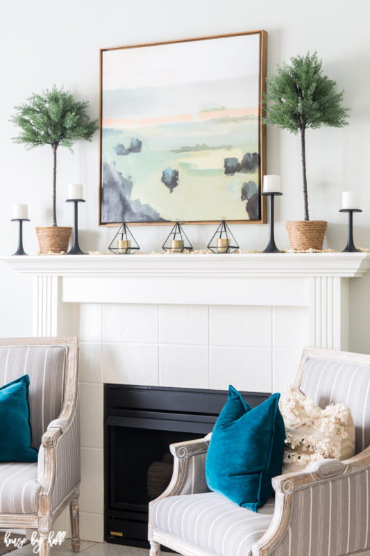 Teal throw pillows are on the armchairs by the fireplace.