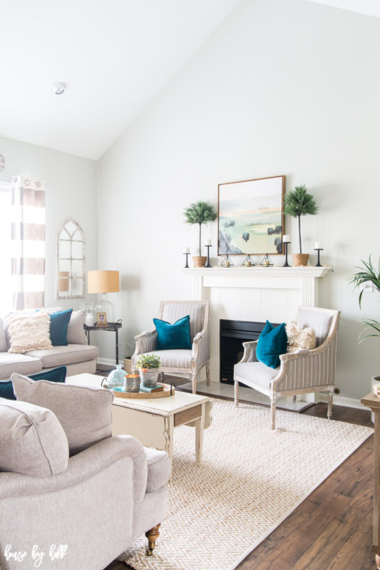 A white rug is in the middle of the living room with a white coffee table on it.