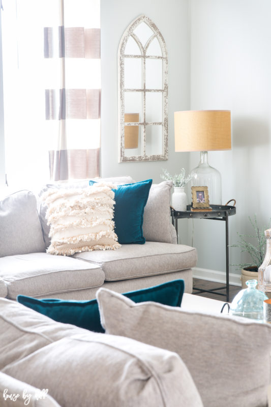 White sectional couches are in the living room with teal pillows.
