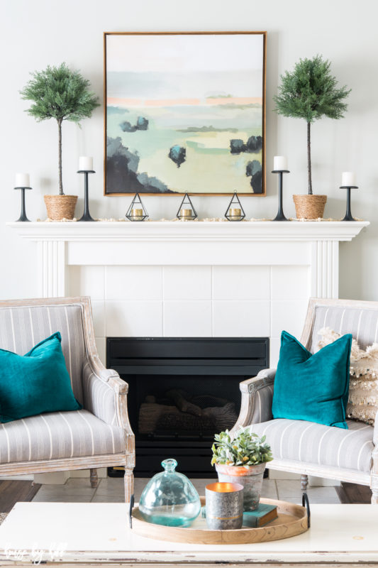 The fireplace mantel with a serene picture above it and topiaries are on either side of the picture.