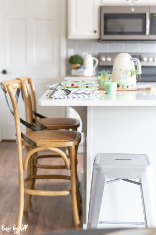 A little white stool is beside the wicker chairs by the kitchen island.