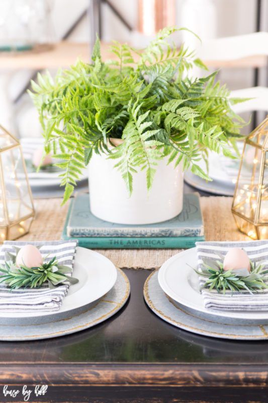 The potted fern is on old books as a centerpiece on the table.
