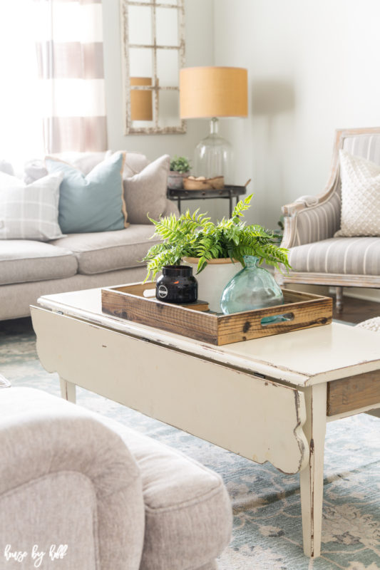 A wooden distressed coffee table with a wooden tray and a green fern.