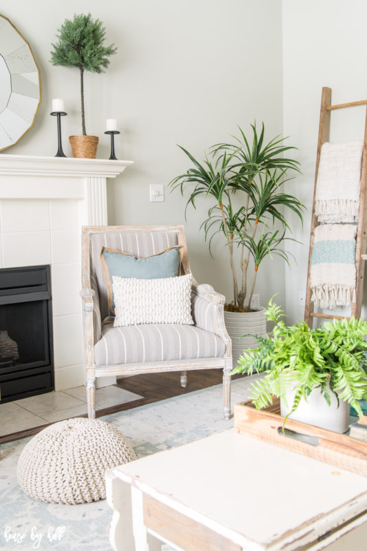 A soft striped neutral chair is in the corner of the room beside the fireplace.