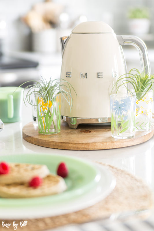 The Smeg kettle and antique glasses filled with greenery.