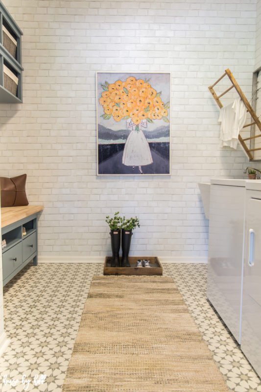 A small bench in the mudroom and a neutral rug in the room as well.