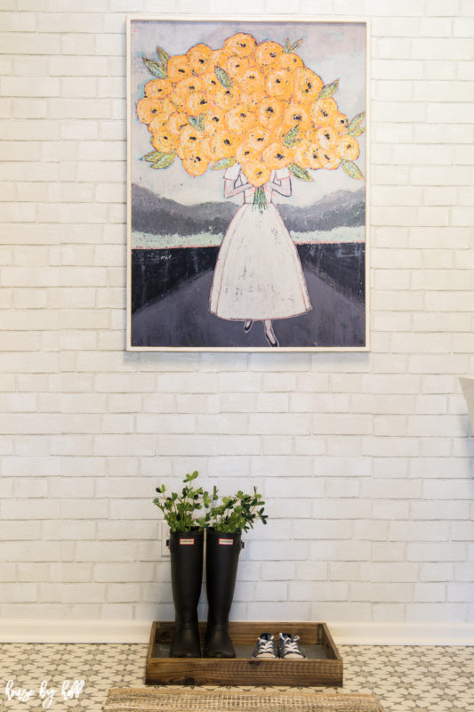 White Painted Brick Removable Wallpaper on the walls, plus a picture of a woman holding flowers and shoes underneath it.