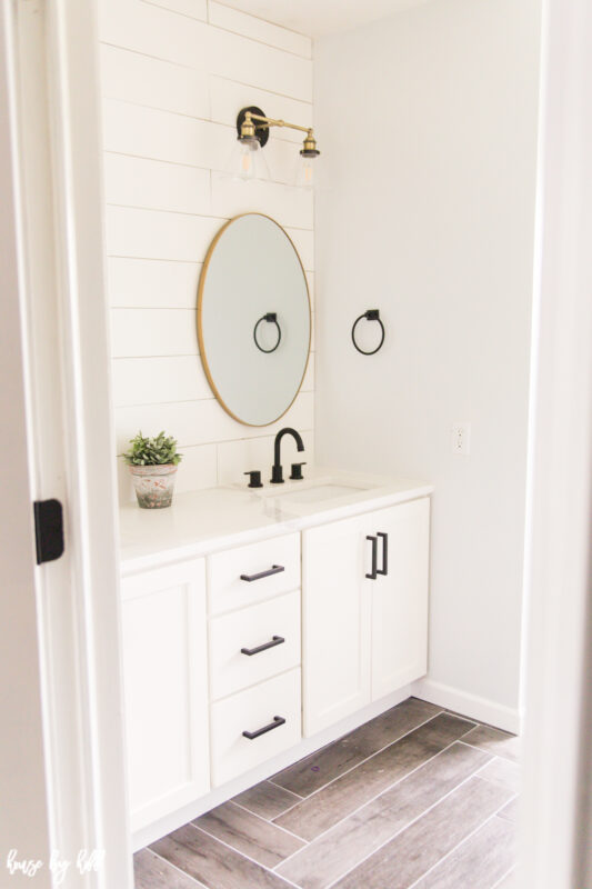 Renovated Guest Bathroom with Shiplap and Brass Light Fixtures