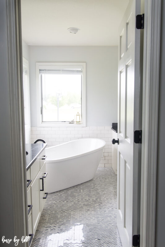 Renovated Master Bathroom with Chevron Tile and Standing Tub