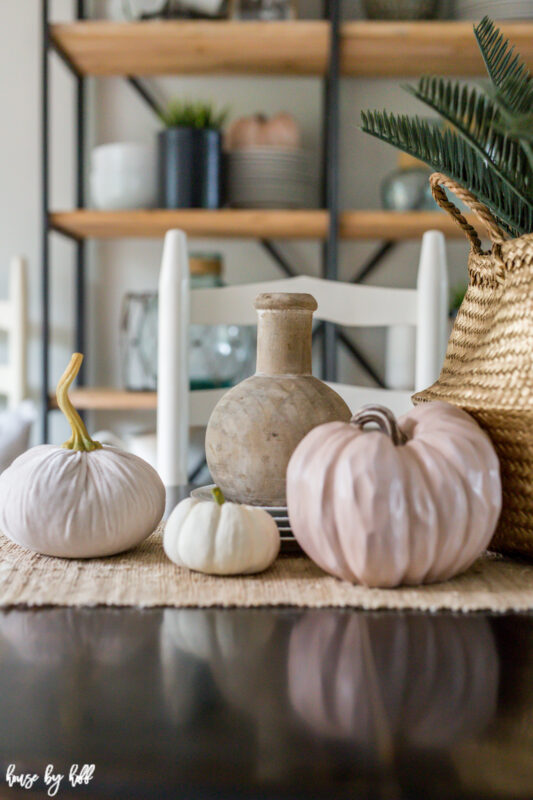 There are three pumpkins, a wooden vase, a stack of plates and a seagrass basket on the table.