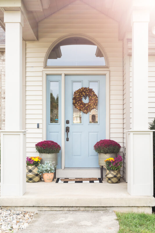 Fall Front Stoop with Blue Door and purple flowers.