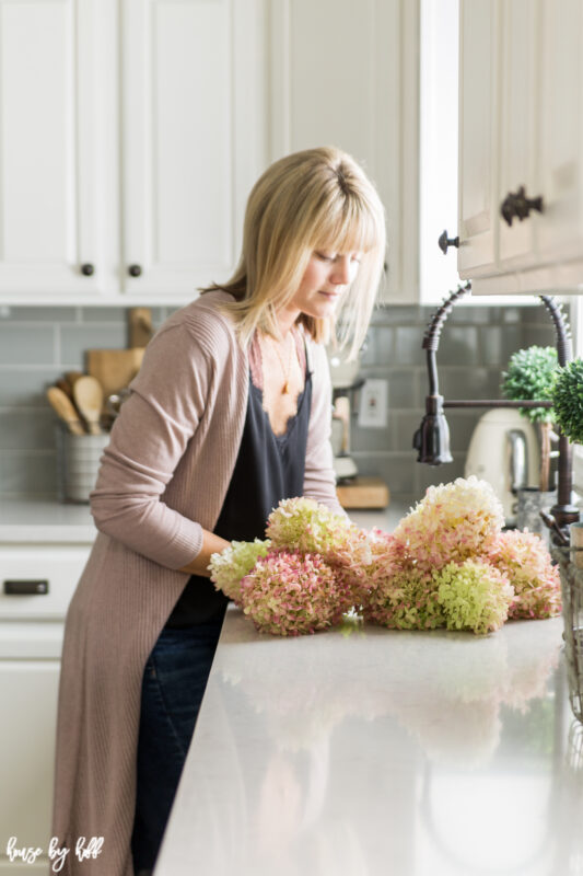 Pink Hydrangeas in the Sink of a Gray and White Kitchen