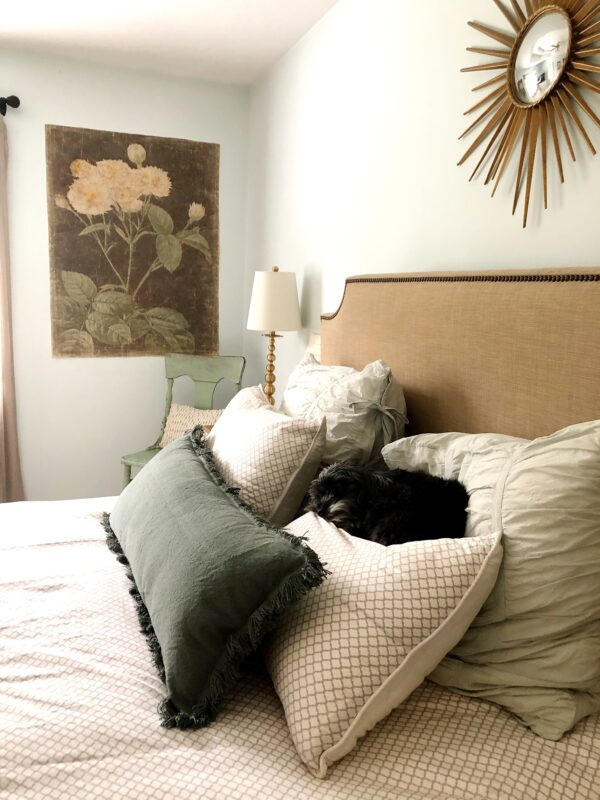 A neutral bed filled with pillows.