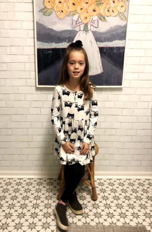 Aprils daughter posing in a black and white dress in front of a picture of a woman holding a bouquet.