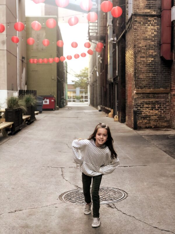 A picture of a little girl in an alley with red patio lanterns strung up.