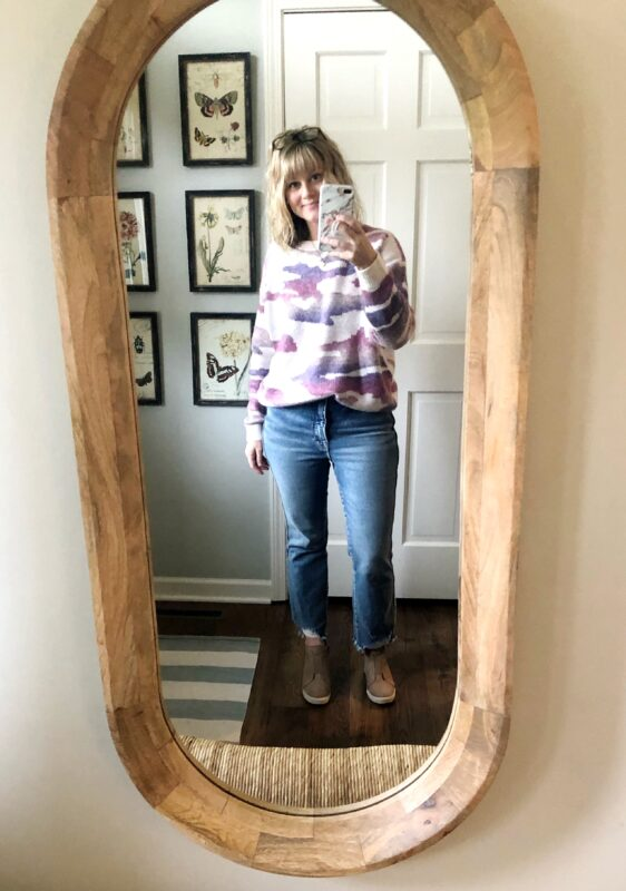 April in jeans, a pink, white and purple sweatshirt, taking a selfie.