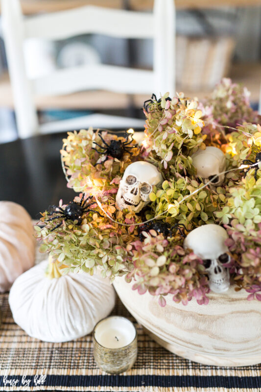 There is a bowl filled with hydrangea in pink and green, with skulls and spiders intertwined.