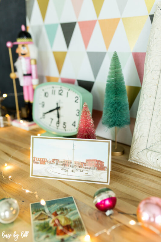 Vintage holiday postcards are on the desk beside the clock.