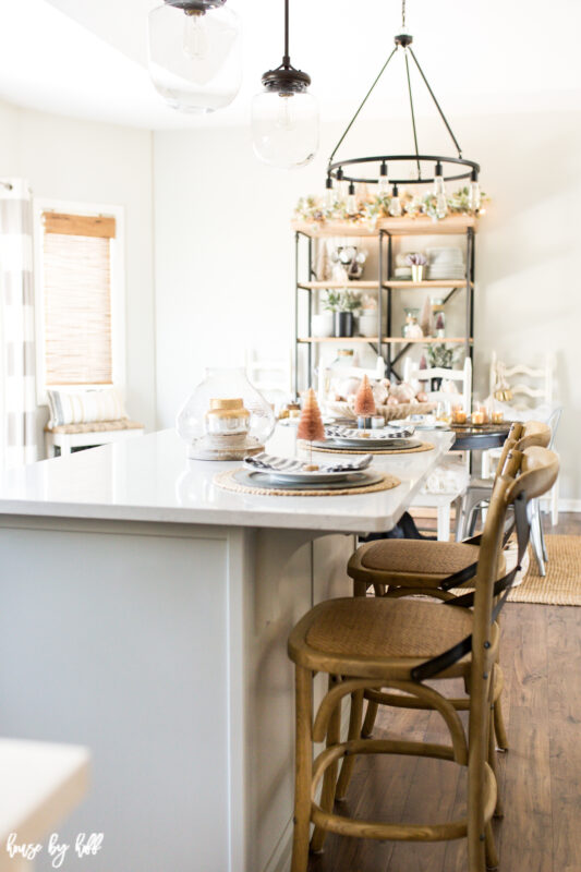 Two chairs are at the kitchen island that has a place setting for two.