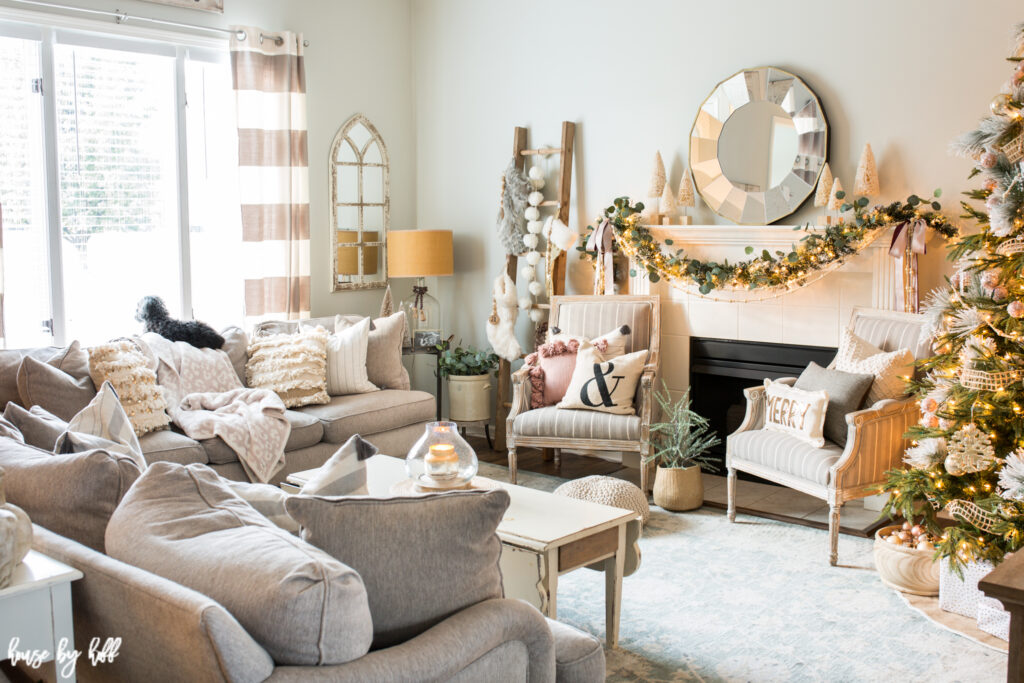 Living Room with Rose Gold and Pink Holiday Decorations and a Christmas tree in the corner of the room.