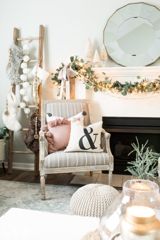 There is an armchair beside the fireplace with neutral and pink throw pillows on the chair.