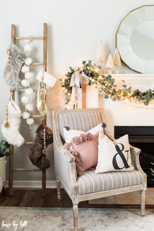 Holiday Mantel with Bottle Brush Trees and Round Mirror Pink Tasseled Pillow in Gray Striped Chair