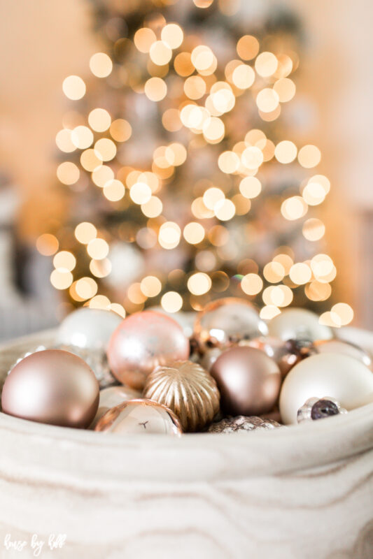 Rose Gold and Cream Ornaments are in a bowl on the coffee table.