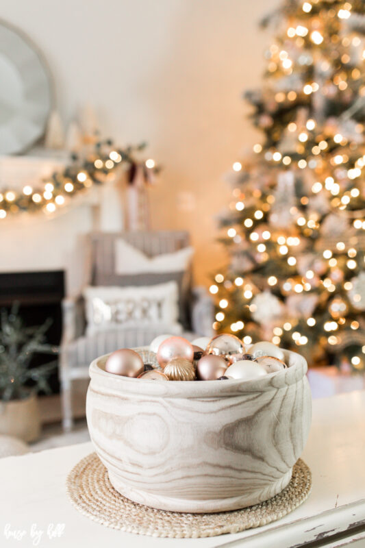 Rose Gold and Pink ornaments are in a wooden bowl on the table.