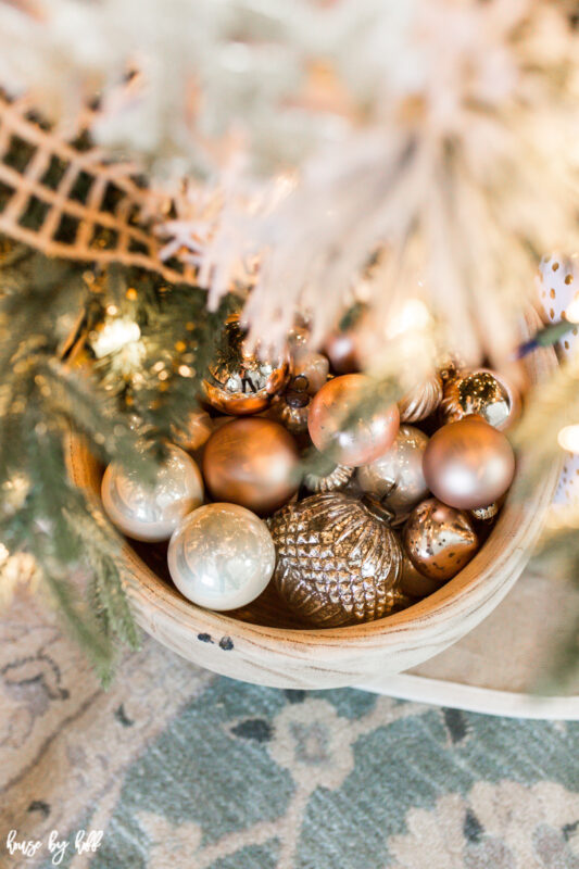 Big Wooden Bowl with Rose Gold and Cream Ornaments beside the Christmas tree.