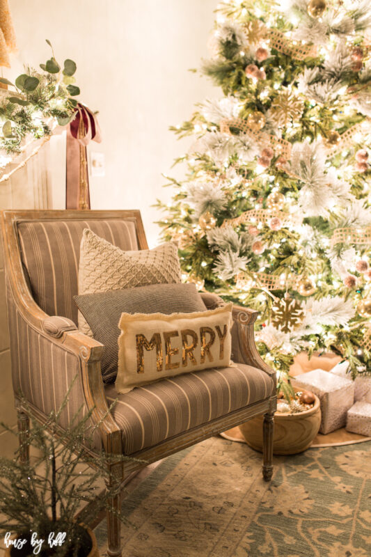 A neutral armchair is beside the tree with throw pillows on it.