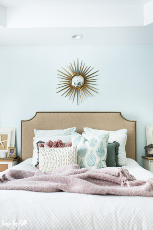 Master Bedroom with Upholstered Headboard and Starburst Mirror