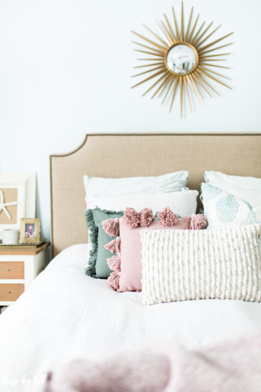 Master Bedroom with Upholstered Headboard, Starburst Mirror, and Pink Accents