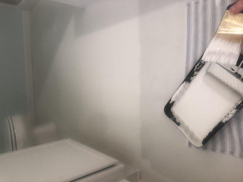 Painting second coat of paint on linoleum bathroom floor