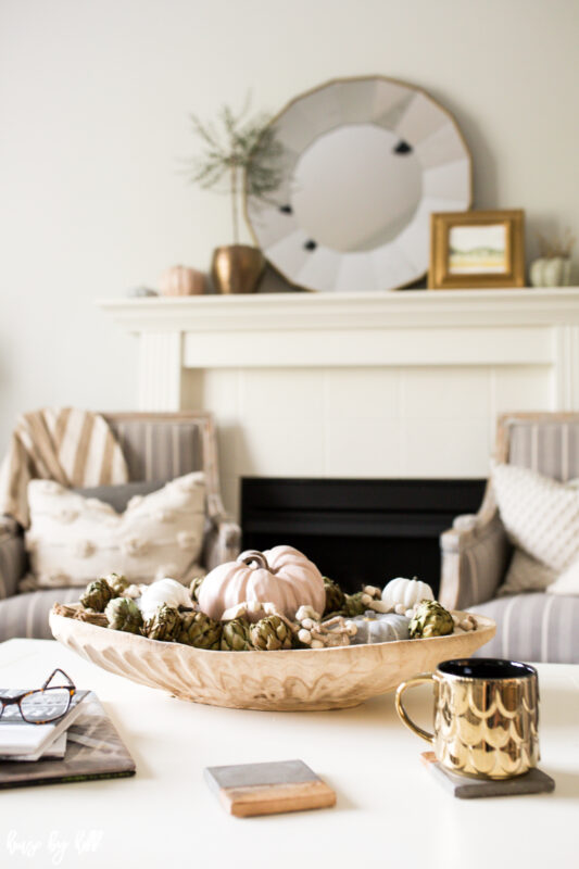 Neutral fall pumpkins on white coffee table with gold mug