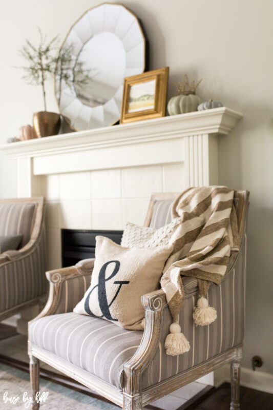 Striped throw on french country armchair and neutral fall mantel