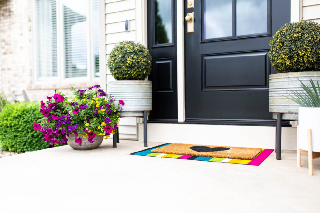 Colorful striped front door mat and flowers on porch