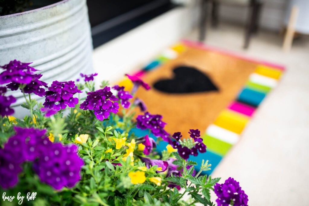 Multicolored flowers and mat on front porch