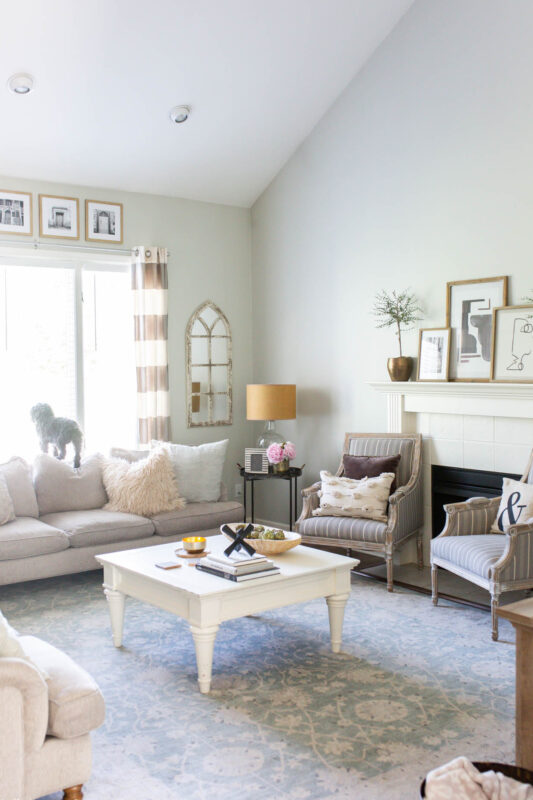 Neutral living room with black and white artwork on mantel